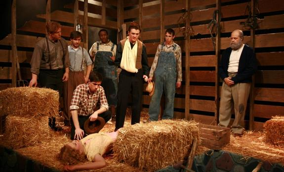 A group of men standing in a barn set and looking down at a young woman on the ground