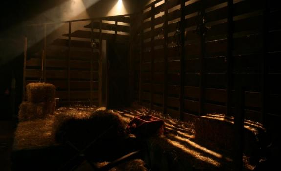 A barn set in a dimly lit theatre