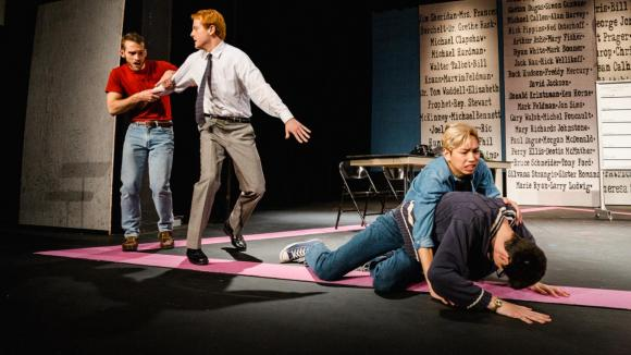 Four actors onstage; one is crouched over another, the third is holding back the fourth