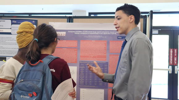 A student presenting a research poster to other students