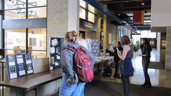 Students viewing posters on a table
