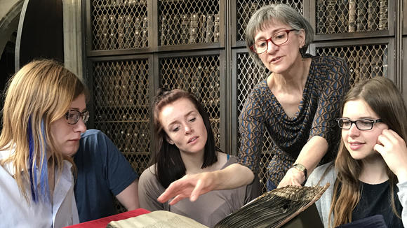 Students looking at a medieval manuscript with Professor Janet Ericksen