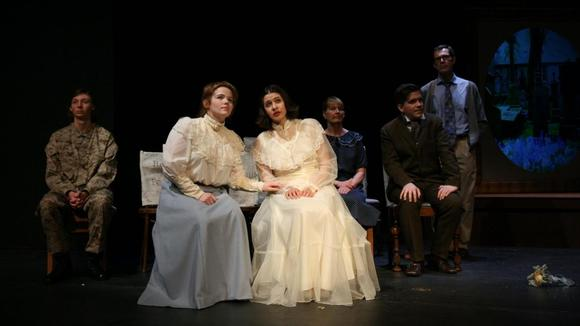 A group of seated actors staring offstage