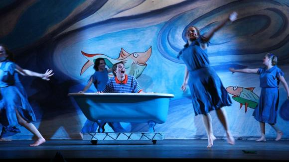 A smiling young man sitting in a bathtub as dancers move around him
