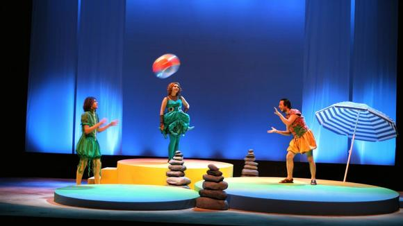 Two young men in bright costumes throwing a beach ball as a young woman dressed as a fish looks on