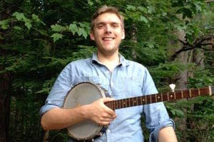A young man holding a banjo