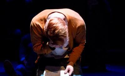 An actor crouches onstage
