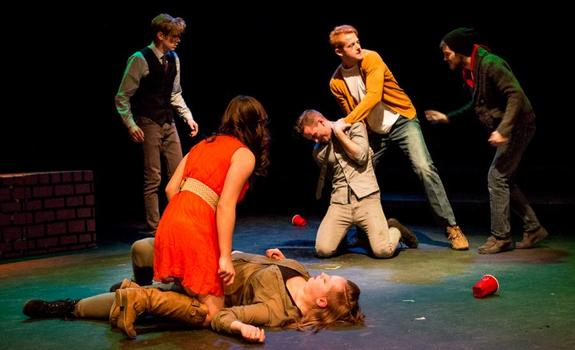 A group of actors crouch and fight onstage
