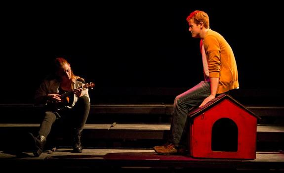 An actor watches an actress play a guitar onstage