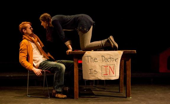 An actress crawls across a table to confront an actor onstage