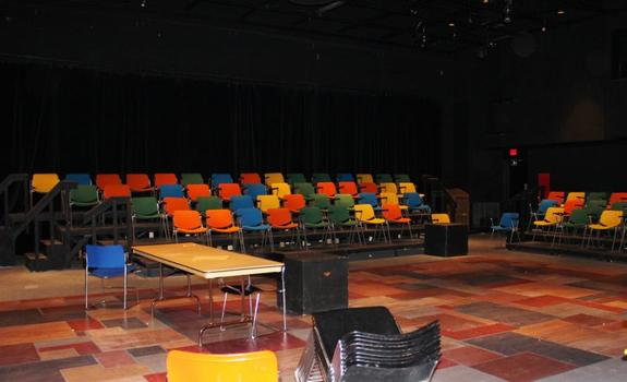 A black room with multicolored theatre seating