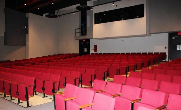 An empty theatre with red seats