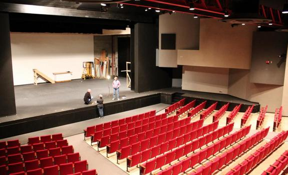 Three adults standing onstage in an empty theatre
