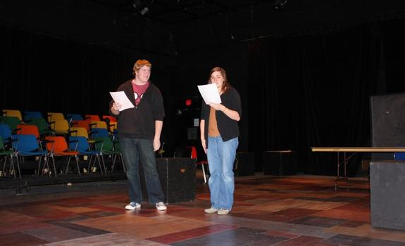 A young man and a young woman reading from scripts