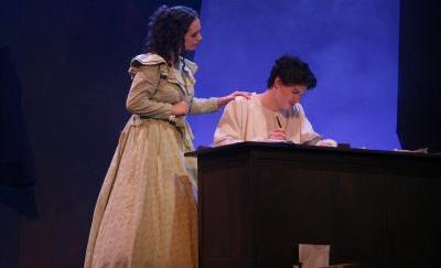 An actor writes at a desk as an actress looks over his shoulder