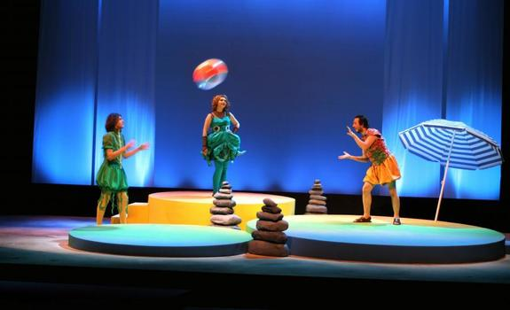Three actors playing with a beach ball onstage